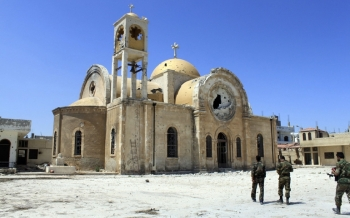 Soldiers loyal to the Syrian regime walk near a damaged church in Qusair, Syria, June 6. (CNS/Reuters/Rami Bleibel)